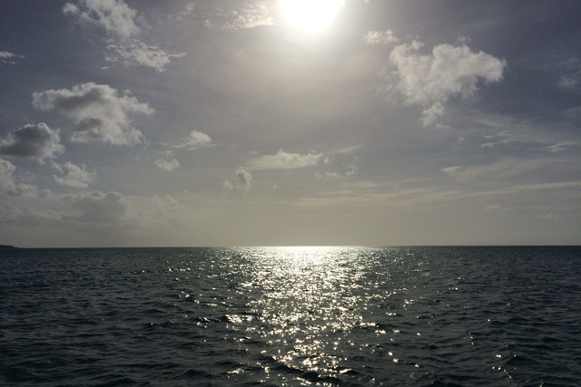 The sun approaching the horizon line over the Caribbean Sea.