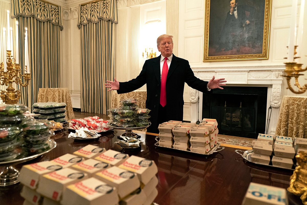 "It looks like Abraham Lincoln is looking over President Trump's shoulder at the burgers on the table thinking, ""Hmm, those look tasty. I wish those were around when I was around."""